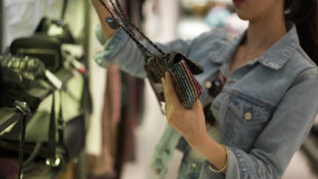 vídeos y material grabado en eventos de stock de close up, woman inspects purse in shopping mall - bolso