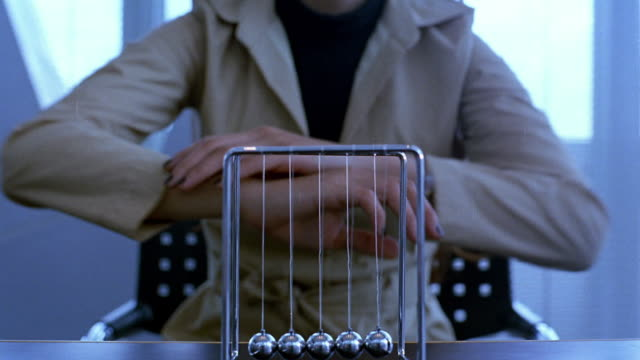 Close up woman leaning forward and watching metal balls move on Newton's Cradle desk toy
