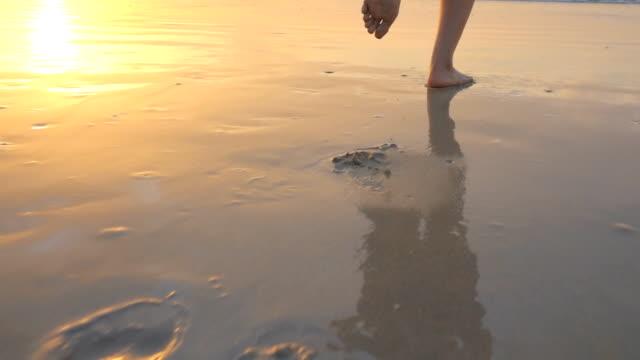 stockvideo's en b-roll-footage met close-up van de benen van de vrouw lopen op het strand - voetafdruk