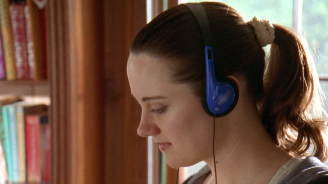 Close up woman listening to walkman while walking on treadmill