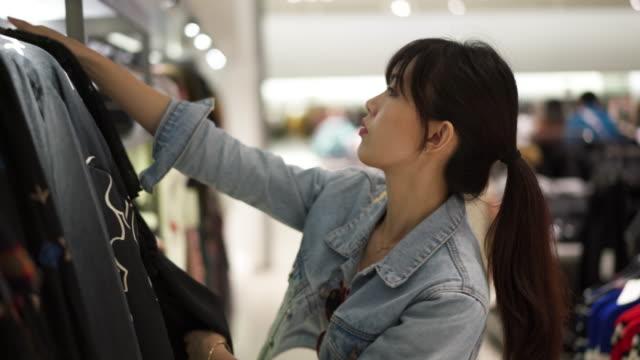 vídeos de stock, filmes e b-roll de close up, woman looks at clothes in chaing mai shopping center - jaqueta jeans