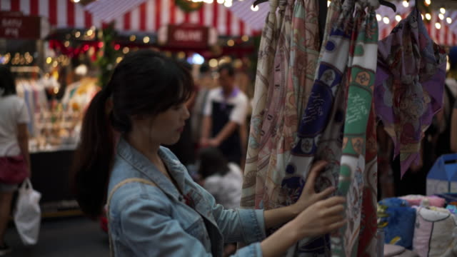 vídeos de stock, filmes e b-roll de close up, woman looks at clothes in chiang mai shopping center - jaqueta jeans