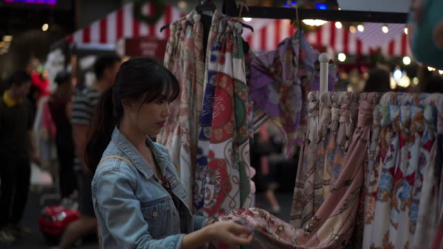 vídeos de stock, filmes e b-roll de close up, woman looks at clothes in thailand shopping mall - jaqueta jeans
