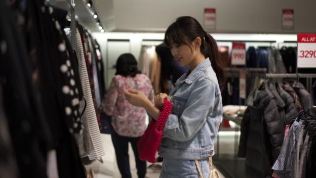 vídeos de stock, filmes e b-roll de close up, woman looks at purse in store - jaqueta jeans