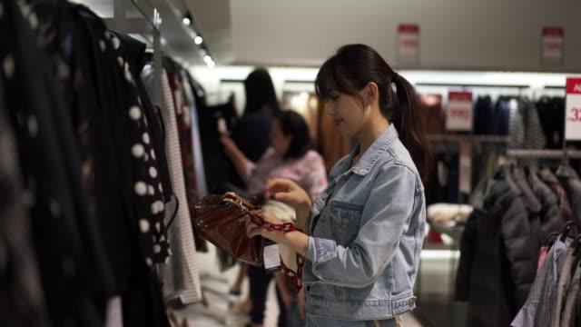 vídeos de stock, filmes e b-roll de close up, woman looks at purse in thailand mall - jaqueta jeans