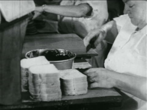 close up woman making sandwiches in school lunch kitchen in wpa project / documentary - documentary footage stock videos & royalty-free footage