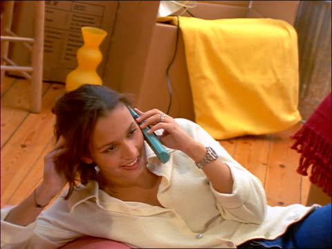 vídeos y material grabado en eventos de stock de close up woman on floor of new home talking on cellular phone / gets excited - 1990