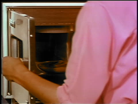 1969 close up woman opening early microwave + removing dish of lobster newburg / industrial - microwave stock videos & royalty-free footage