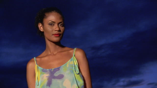 vidéos et rushes de close up woman posing with dark sky in background - kelly mason videos