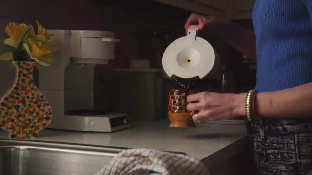 close up - woman pours coffee from a retro mr. coffee coffee pot. - bricco per il caffè video stock e b–roll