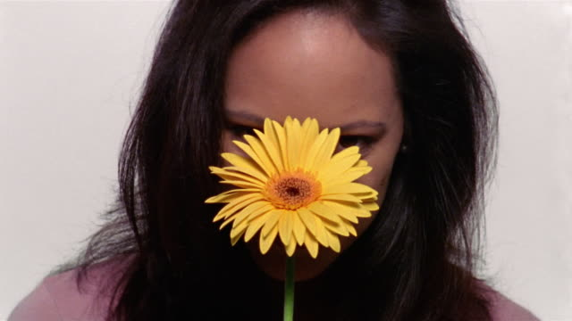 Close up woman raising head and touching her face with flower