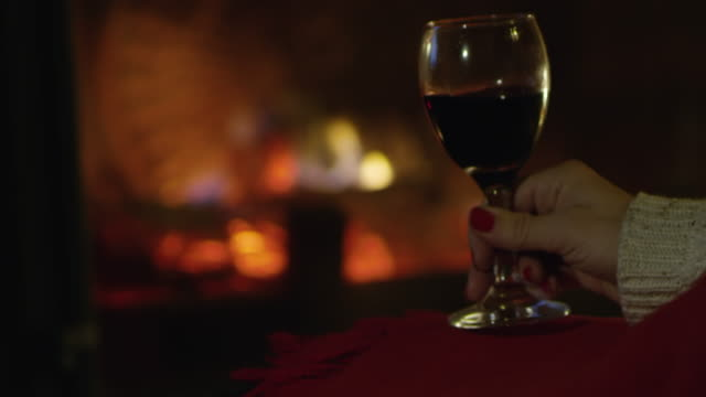 4K Close up woman relaxing, drinking red wine by cozy fireplace, slow motion