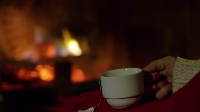4K Close up woman relaxing, drinking tea by cozy fireplace, slow motion
