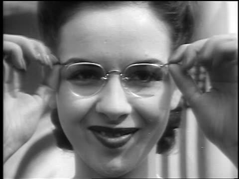 stockvideo's en b-roll-footage met b/w 1941 close up woman removes glasses smiles crosseyed / palisades park nj / newsreel - 1941
