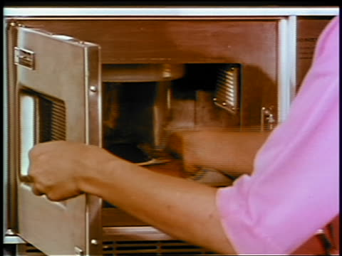 1969 close up woman removing plate of chocolate cake from early microwave / industrial - microwave stock videos & royalty-free footage