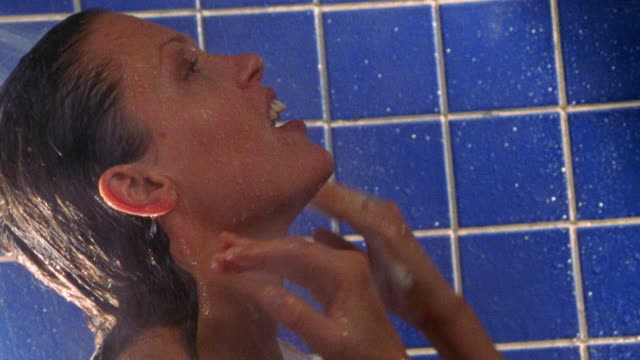 close up woman rinsing hair in shower
