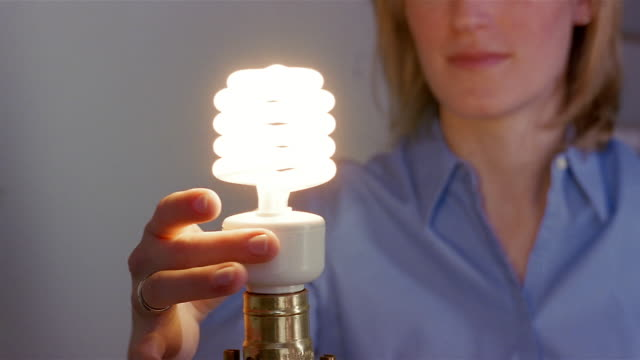 close up woman screwing energy efficient light bulb into lamp - elektrische lampe stock-videos und b-roll-filmmaterial