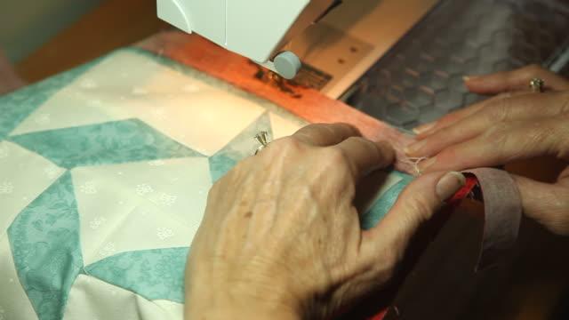 vídeos de stock e filmes b-roll de close-up mulher costurar coberta acolchoada - edredão