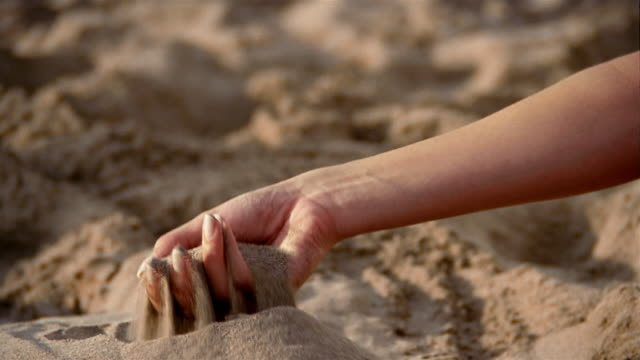vídeos de stock e filmes b-roll de close up woman sifting sand through her hand - areia