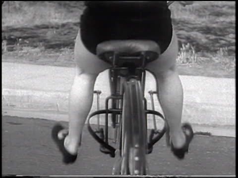 B/W 1933 REAR VIEW close up woman sitting in bouncing stationary bicycle seat / San Francisco, California / newsreel