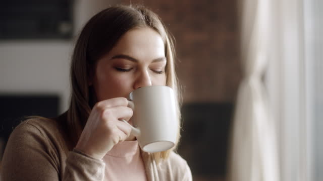 close up, woman sitting in living room and drinking coffee - attività del fine settimana video stock e b–roll