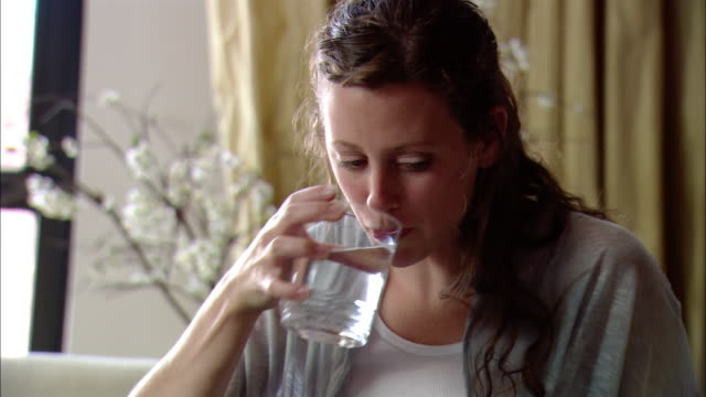 close up woman sitting on sofa drinking water / putting glass down on coffee table - coffee table stock videos & royalty-free footage