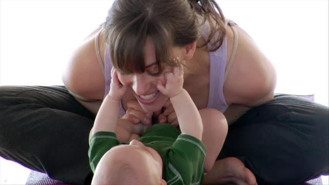 close up woman sitting on yoga mat and playing with baby/ brooklyn, new york - babygro stock videos & royalty-free footage