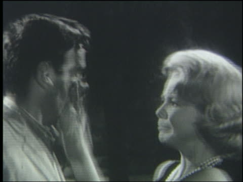 B/W 1962 close up woman slaps man in face; they turn to look at someone off-screen