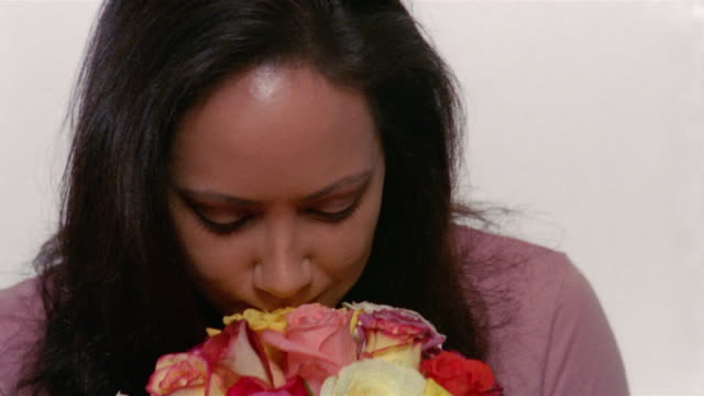 Close up woman smelling bouquet of roses