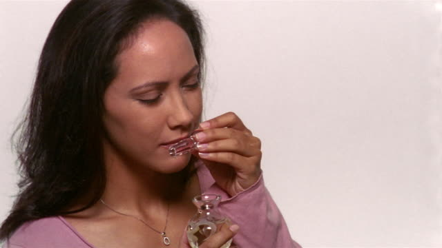 close up woman smelling stopper from perfume bottle - smelling stock videos & royalty-free footage