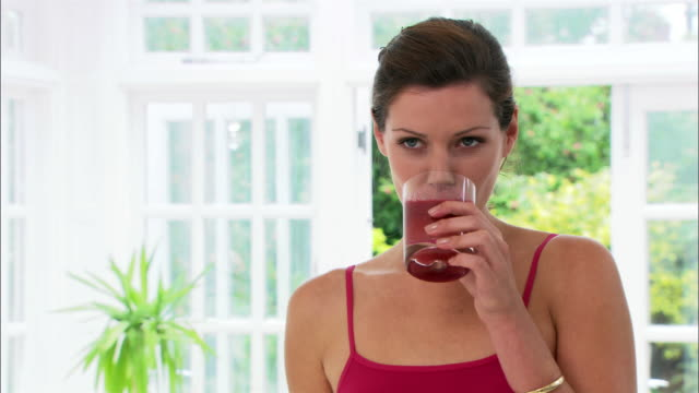 close up woman smiling and drinking fruit smoothie/ london - smoothie stock videos & royalty-free footage