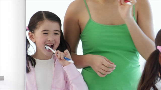 close up woman squirting toothpaste on daughter's toothbrush/ woman and daughter brushing teeth in mirror/ brooklyn, new york - squirting woman stock videos and b-roll footage