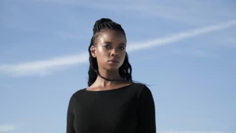 close up, woman stands in desert on clear day - afroamerikanskt ursprung bildbanksvideor och videomaterial från bakom kulisserna