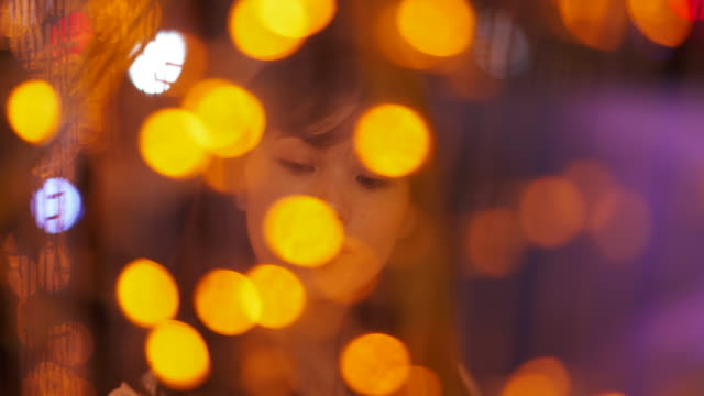 Close up, woman surrounded by holiday lights