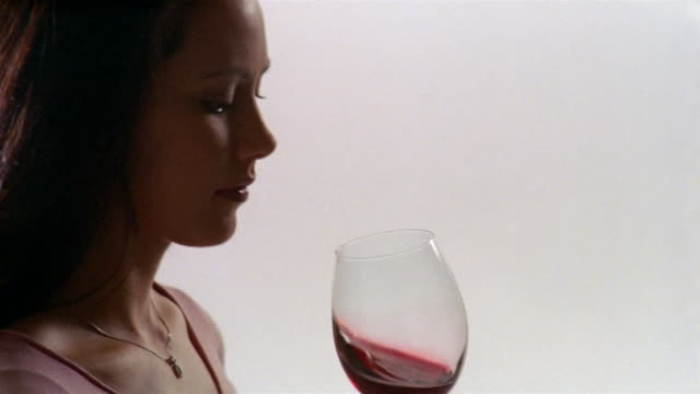 Close up woman swirling red wine around glass and smelling it