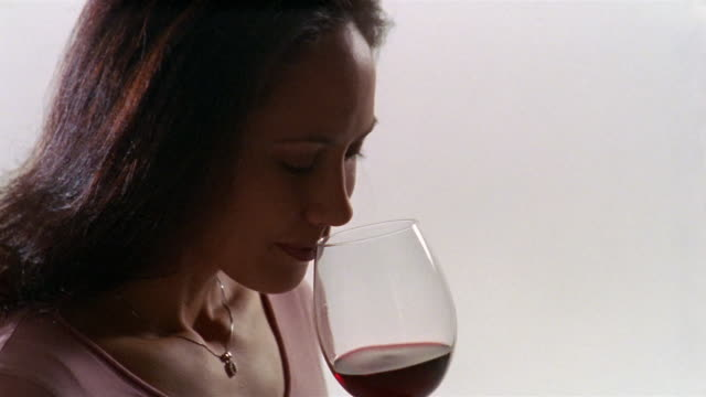close up woman swirling red wine around glass and smelling it - smelling stock videos and b-roll footage