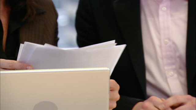 close up woman talking in board room/ tilt down man passing papers to woman/ woman shuffling papers/ tilt up woman talking/ pan man turning head/ new york, new york - shuffling stock videos and b-roll footage