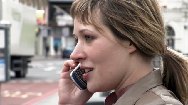 close up woman talking on mobile phone on busy street/ tilt down woman's purse/ tilt up woman talking/ london - hanging up stock videos & royalty-free footage