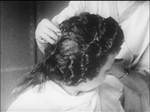 b/w 1919 close up woman turning head of woman with permanent wave in beauty parlor / newsreel - 1910 1919 stock videos & royalty-free footage