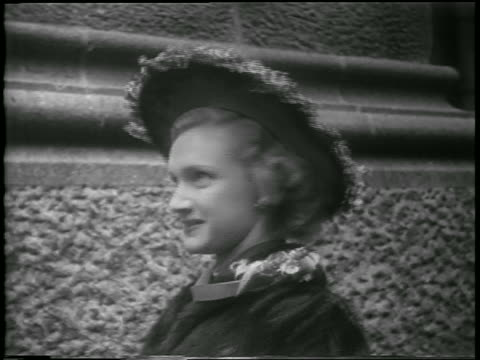b/w 1952 close up woman turning to show easter bonnet with flowers outdoors / nyc / newsreel - 1952 stock videos & royalty-free footage