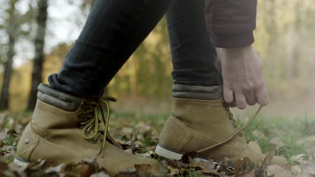 vídeos de stock, filmes e b-roll de close-up, mulher amarrar cadarços nas folhas outonais - ponto de vista de caminhada