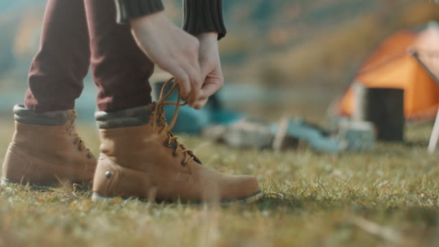 close up, woman tying shoelaces - zaino da montagna video stock e b–roll