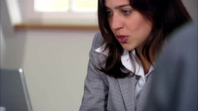 stockvideo's en b-roll-footage met close up woman typing on laptop/ tilt up woman in business meeting talking to man as she looks at laptop/ munich, germany - formele zakelijke kleding