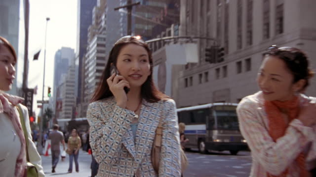 stockvideo's en b-roll-footage met close up woman walking and talking on mobile phone / zoom out women putting on sunglasses / new york city - 2004