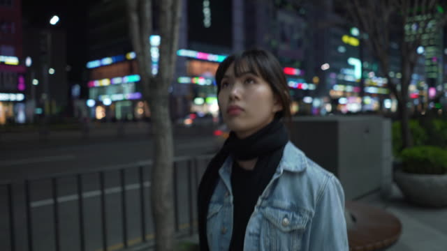 Close up, woman walks in Seoul at night