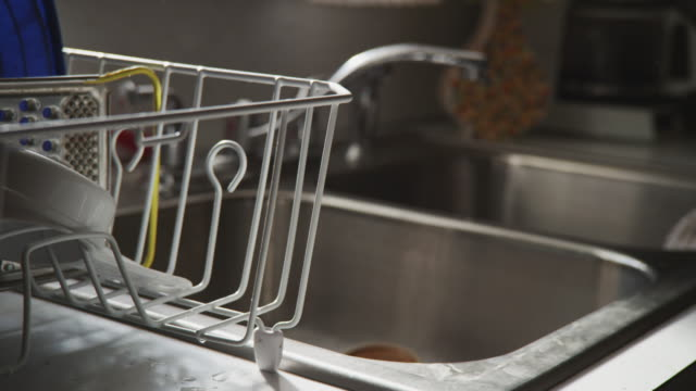 close up - woman washes drinking glass at a kitchen sink, places it in a drying rack. - drying rack stock videos and b-roll footage
