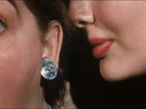 1953 close up woman wearing bright lipstick whispering into woman's ear