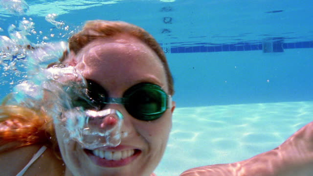 close up woman wearing goggles, smiling and waving at camera underwater - swimming goggles stock videos & royalty-free footage