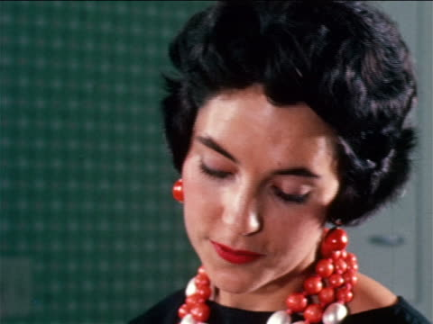 1950 close up woman wearing large beaded necklace + matching earrings / industrial - anno 1950 video stock e b–roll