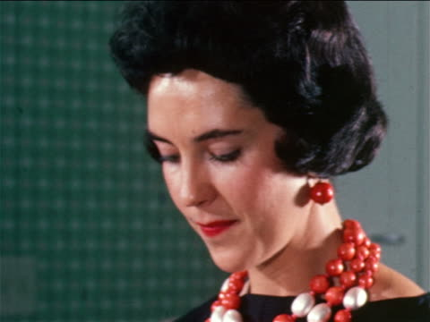 1950 close up woman wearing large beaded necklace smiling / industrial - orecchini video stock e b–roll
